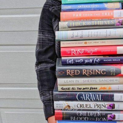 Rachael holding gigantic stack of books