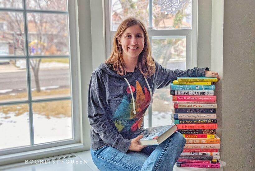 Rachael the Booklist Queen with a book stack from her 2020 Reading List
