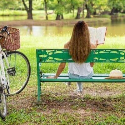Woman reading book, bench, pond, summer hat, bicycle