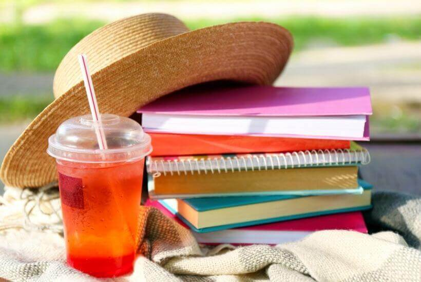 summer hat, book stack, drink with straw