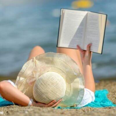 Best Beach Reads 2021 - woman in sun hat on beach reading a book