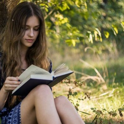 girl leaning against tree reading book