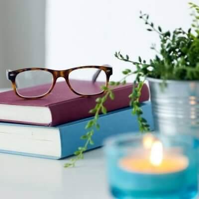 nonfiction books, glasses, candle, plant