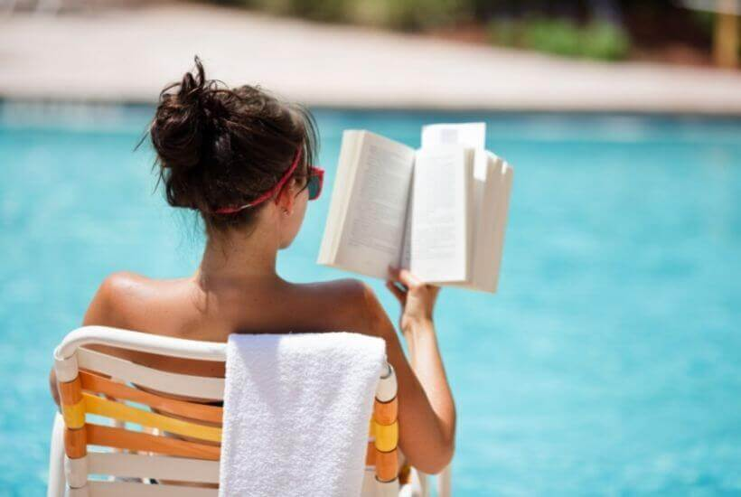 woman reading by pool