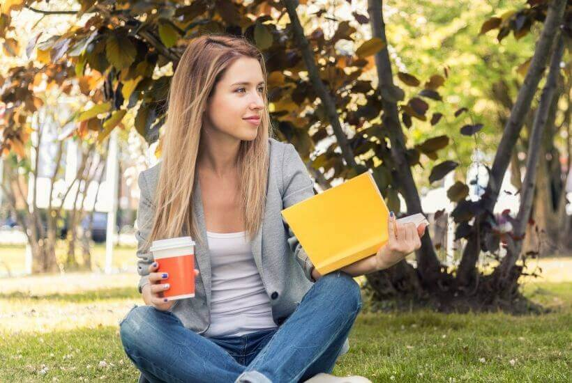 woman reading book and holding coffee