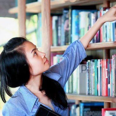 Teen Girl Choosing Book