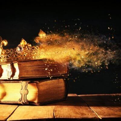 gold crown on two books with gold glitter