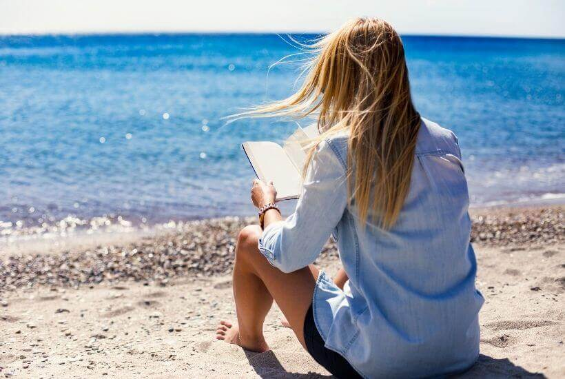 woman reading book on beach