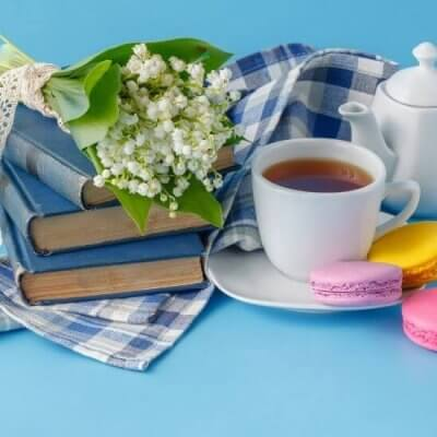 literary books with blue covers stacked, white flowers, teapot, tea cup, macarroons, blue background