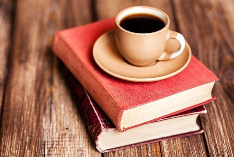 two books and cup of coffee on wood table