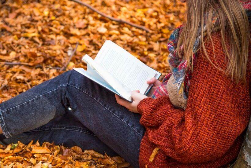 Woman in red sweater reading book among pile of leaves