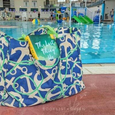 beach bag at pool with book The Last Thing He Told Me by Laura Dave