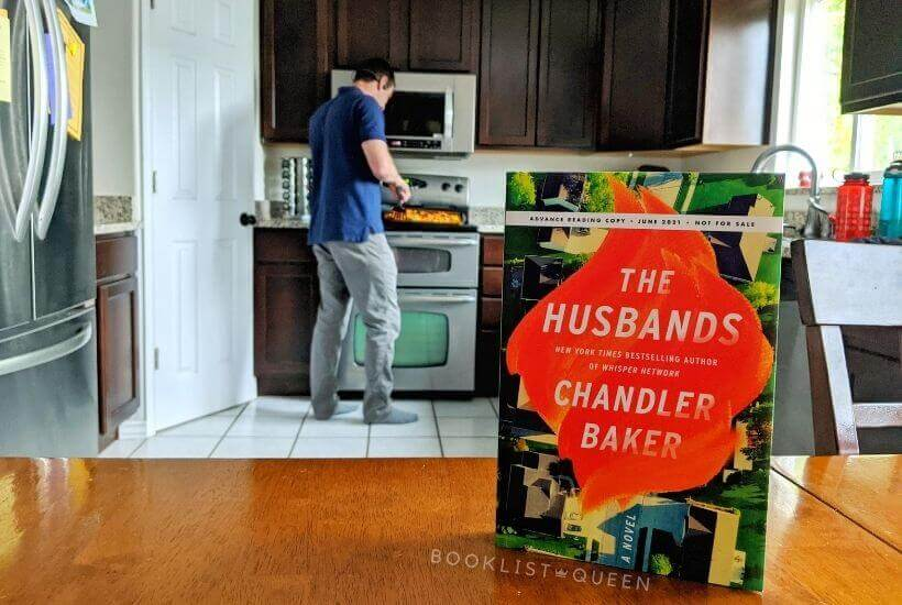 book The Husbands by Chandler Baker with my husband cooking dinner in the background