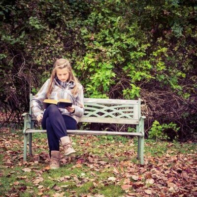 Woman on bench reading book, fall reading