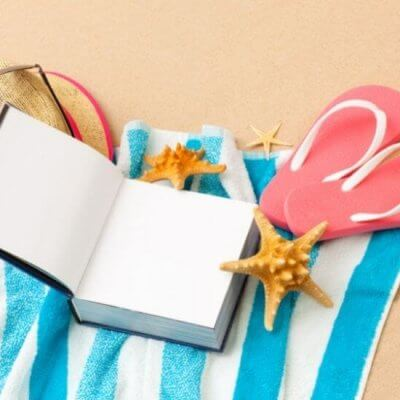 book on towel on sand, flip flops, sea star, beach hat