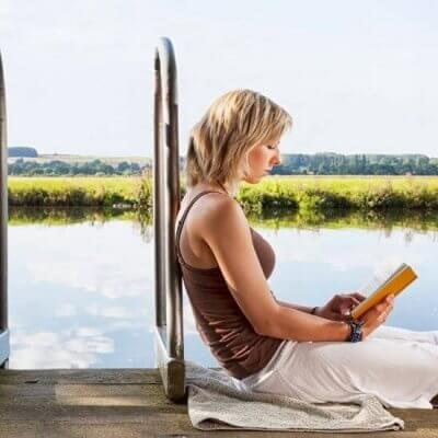 woman on dock reading a book