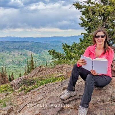 Rachael reading on top of a mountain